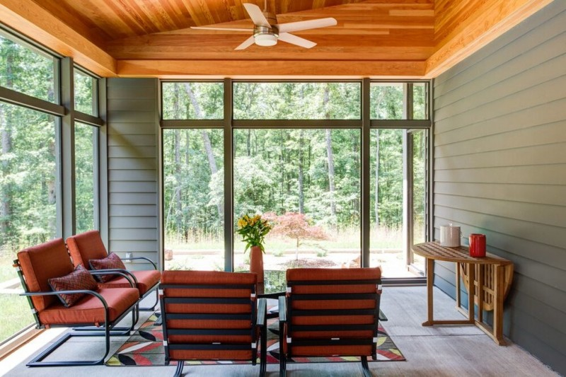 farmhouse style sunroom in Origami House contemporary living room set wood drop leaf table pale toned wood floors grey wood siding walls wood standard ceilings