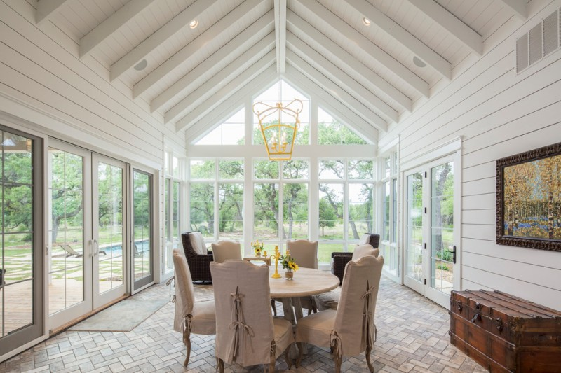 grand farmhouse sunroom with slanted roofs soft toned dining furniture rustic case as the decorative storage tiles floorings