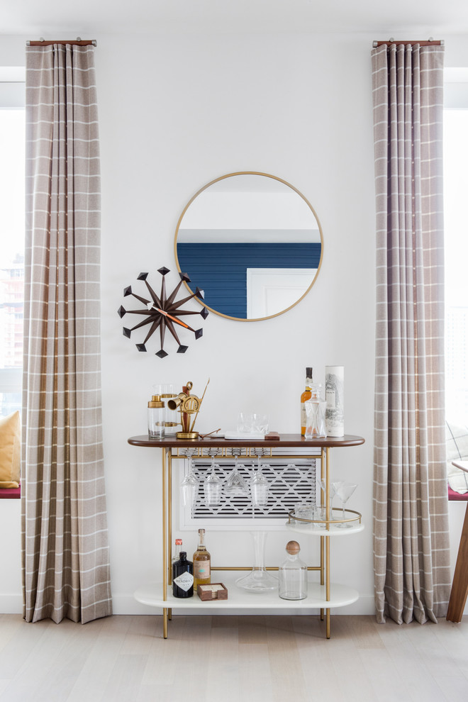 midcentury bar cart idea with gold finishing details on cart and decorative mirror
