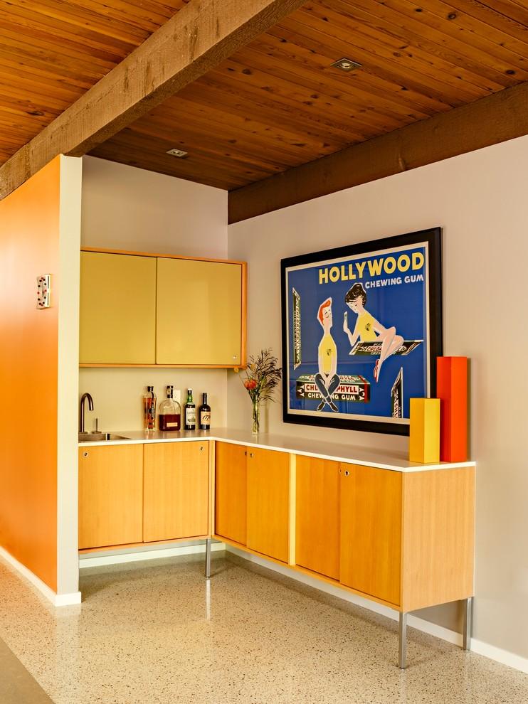midcentury modern bar kitchen L shaped white countertop medium toned wood flat panel cabinets pop styled wall decor beige laminated floors