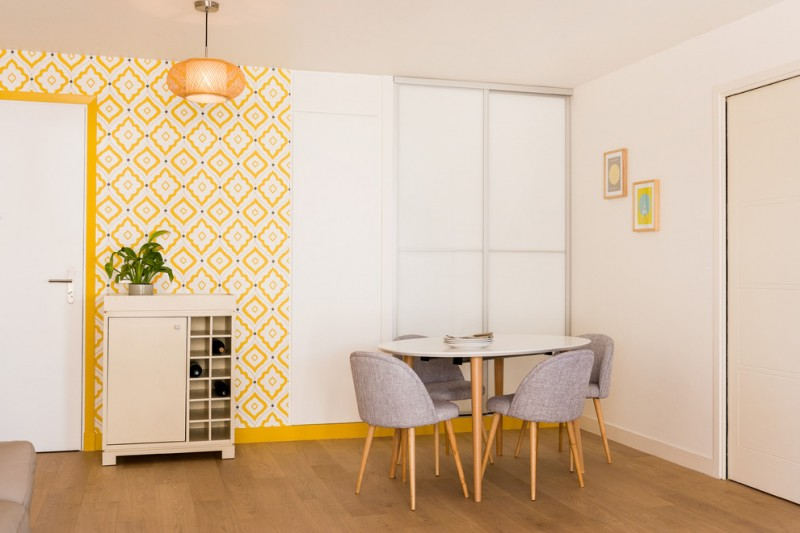 midcentury modern dining room midcentury modern dining chairs white & round top dining table white finishing wine storage yellow wallpaper medium toned wood floors