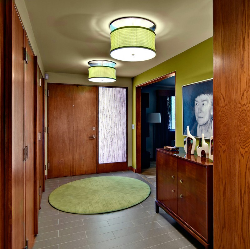 midcentury modern entryway dark wood front door with side window grey tiles floors green walls round shaped rug in green large pendant lamps with green shades dark wood hall console