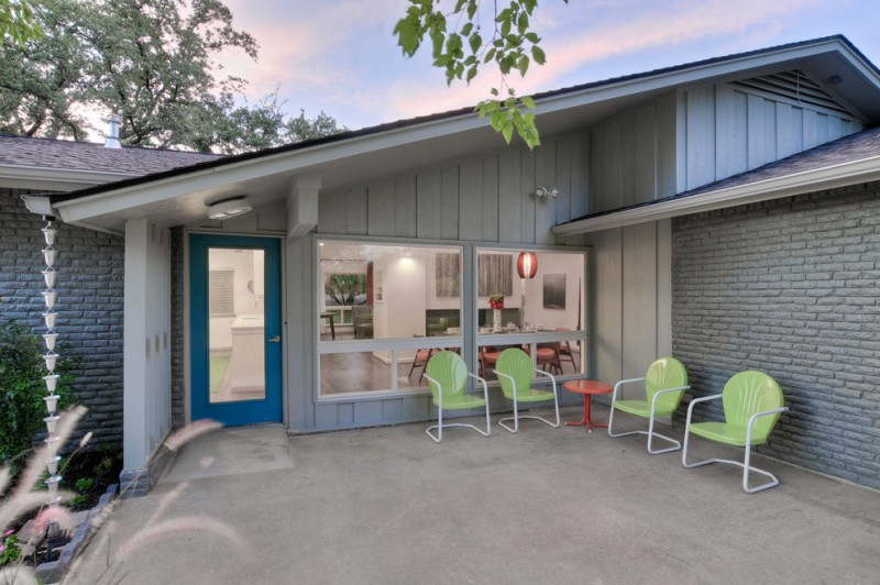 midcentury modern exterior in grey large glass windows blue trimed front door green chairs red side table