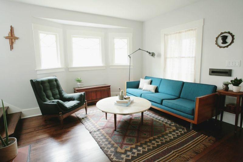 midcentury modern living room turquiso sofa dark green armchair dark toned wood floors traditional area rug