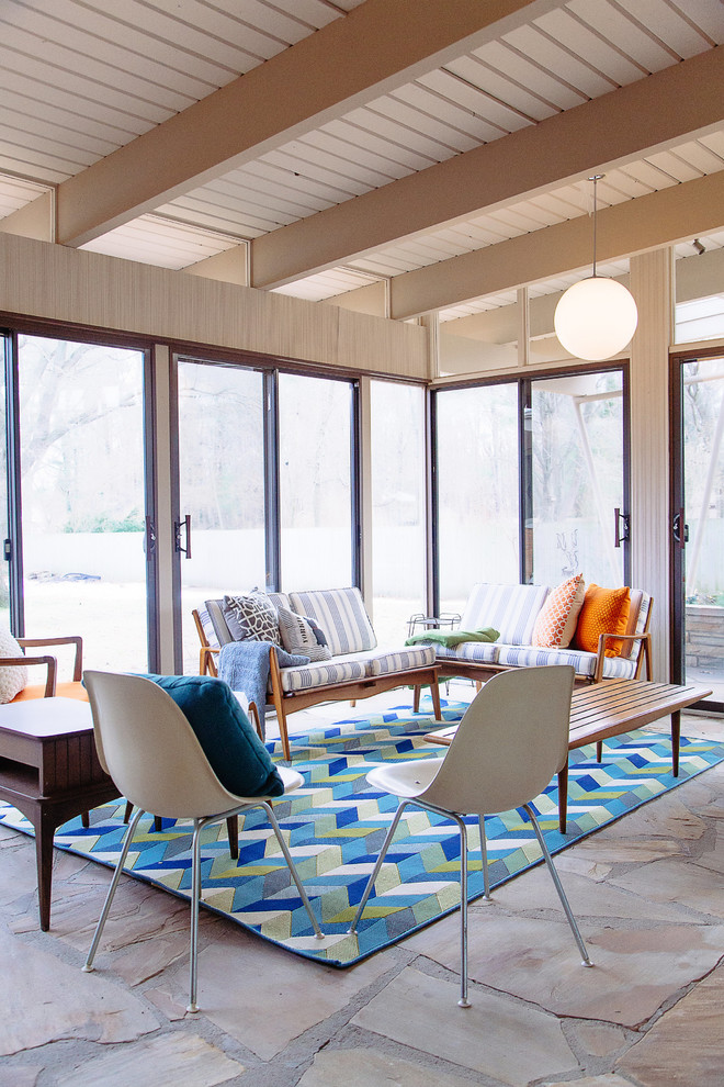 midcentury modern sunroom glass door and windows multicolored area rug slate floors two midcentury modern side chairs in white wood bench two loveseat with throw pilows