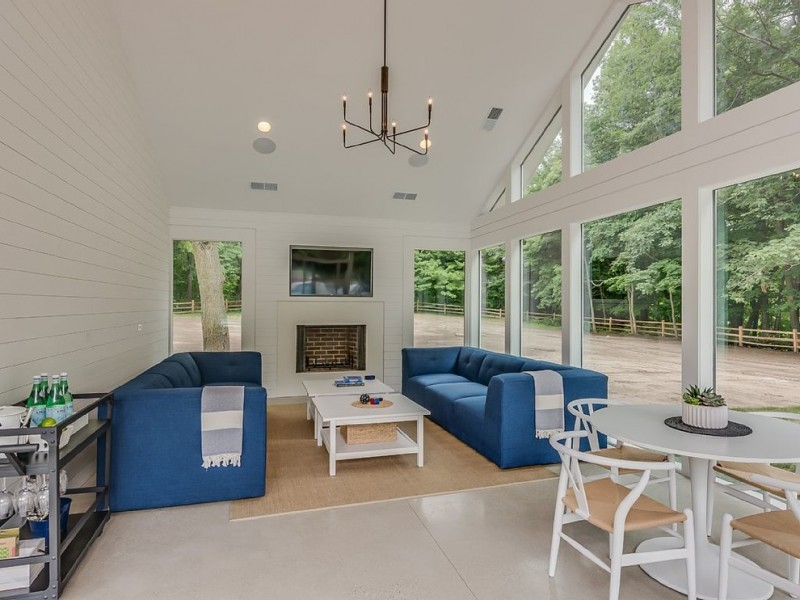 modern & clean lines sunroom with white interior modern blue couches modern white center tables cream area rug white polished concrete floors white wood siding walls