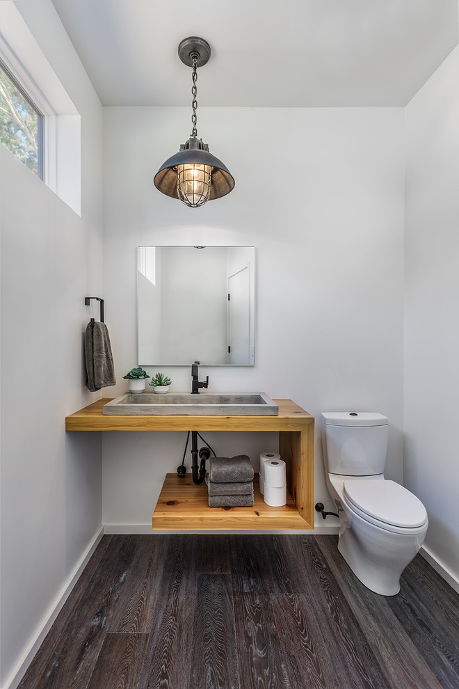 modern rustic bathroom vanity with wood counter and open shelf concrete sink white toilet frameless mirror rustic style pendant grey wood wood floors