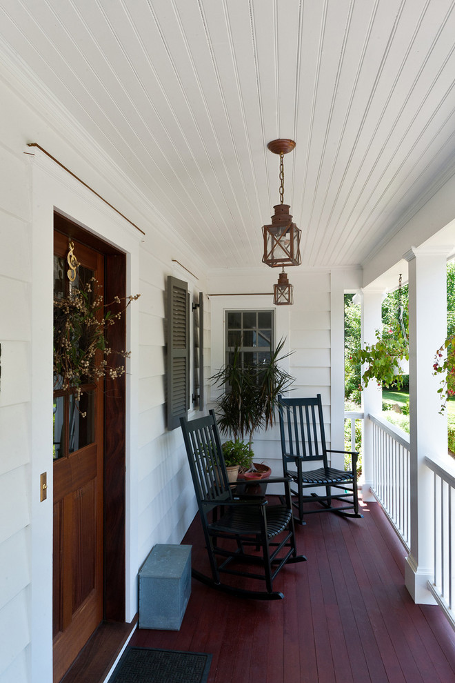 narrow traditional front porch a pair of black finishing rocking chairs dark finishing wood siding floors white painted wood siding exterior walls traditional pendants white wood railings