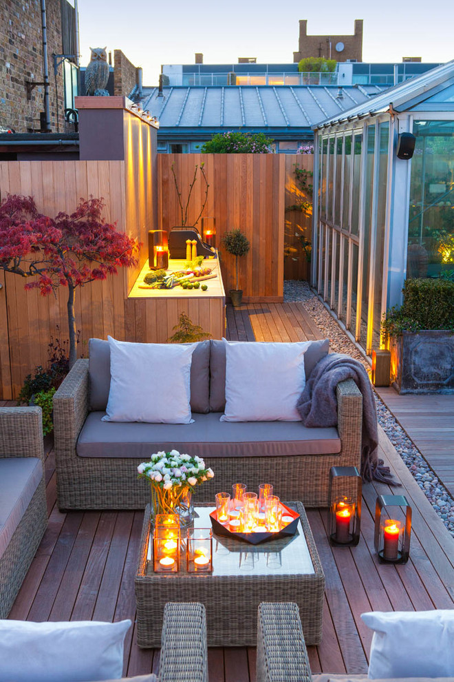 roof terrace design loveseat with white throw pillows grey throw blanket glass top center table wood board decking floors modern lanterns clusters of candles