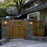 Rustic Front Gate Made Of Natural Stone Rail Posts And Wooden Front Gate's Door A Pair Of Traditional Wall Sconces