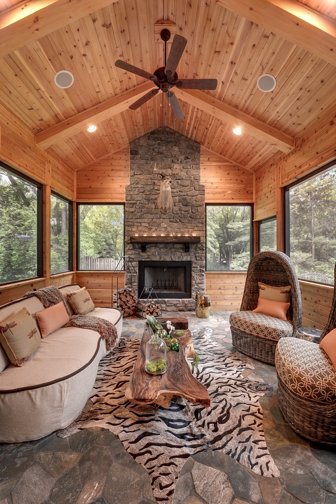 rustic sunroom design wood vaulted ceilings outdoor fireplace with shabby brick surround animal print area rug white sofa unique chairs