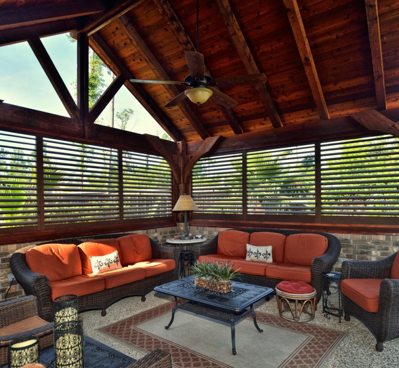 rustic sunroom with window blinds and side skylight dark toned living room set with orange seaters granite floors traditional rug