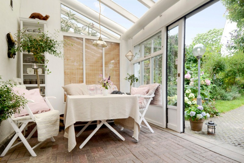 scandinavian sunroom in white clear glass roof with white painted supports sliding glass door brick floors white outdoor dining furniture with x base
