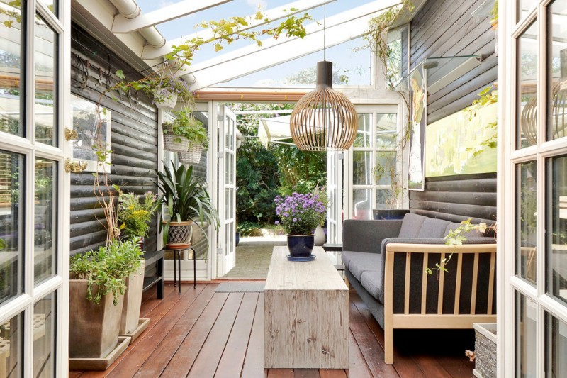 scandinavian sunroom with growing plants addition wood board floors black couch with wood construction black siding walls clear glass roofs decorative pendant