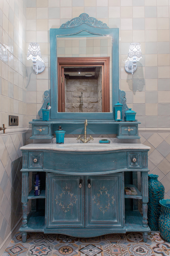 shabby chic bathroom vanity in blue with marble countertop undermount sink and mirror multicolored tiles floors ceramic tiles walls a pair of white wall sconces