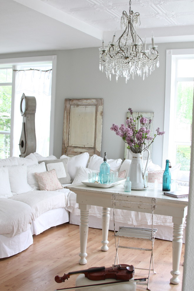 shabby chic living room idea white sofa slipcover white painted table small chair in white medium toned wood floors crystal chandelier