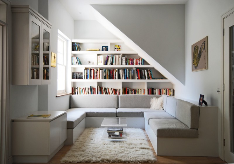 small contemporary reading nook U shaped sectional in white large book shelves medium sized fluffy rug in white