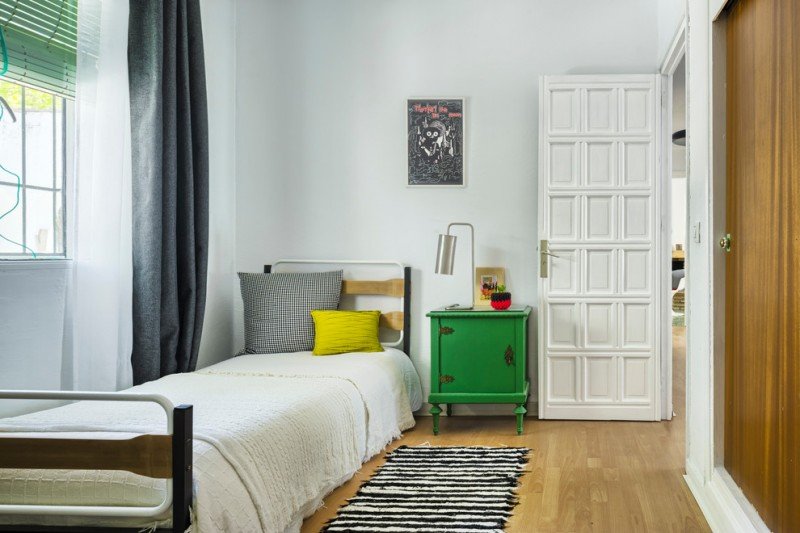 small mediterranean guest room single bed with headboard green painted bedside table white black stripes mat medium toned wood floors