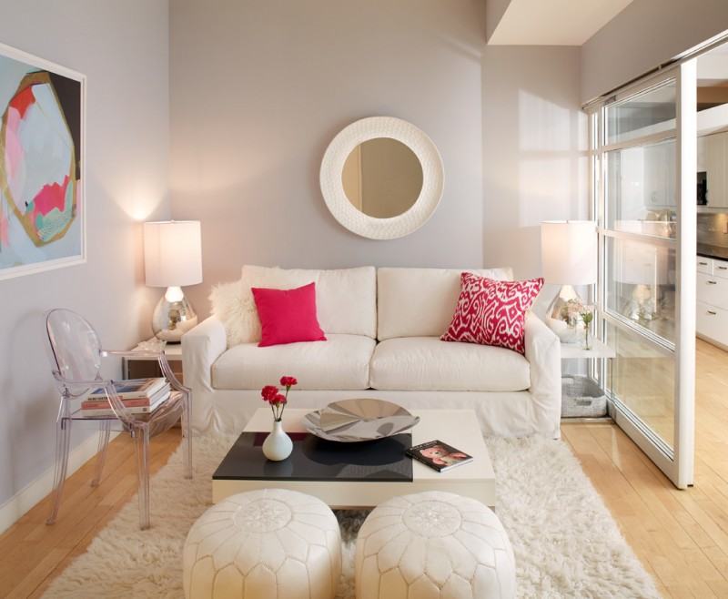 small sized contemporary living room white loveseat red throw pillows white fluffy rug two white ottomans clear acrylic light grey walls light wood floors
