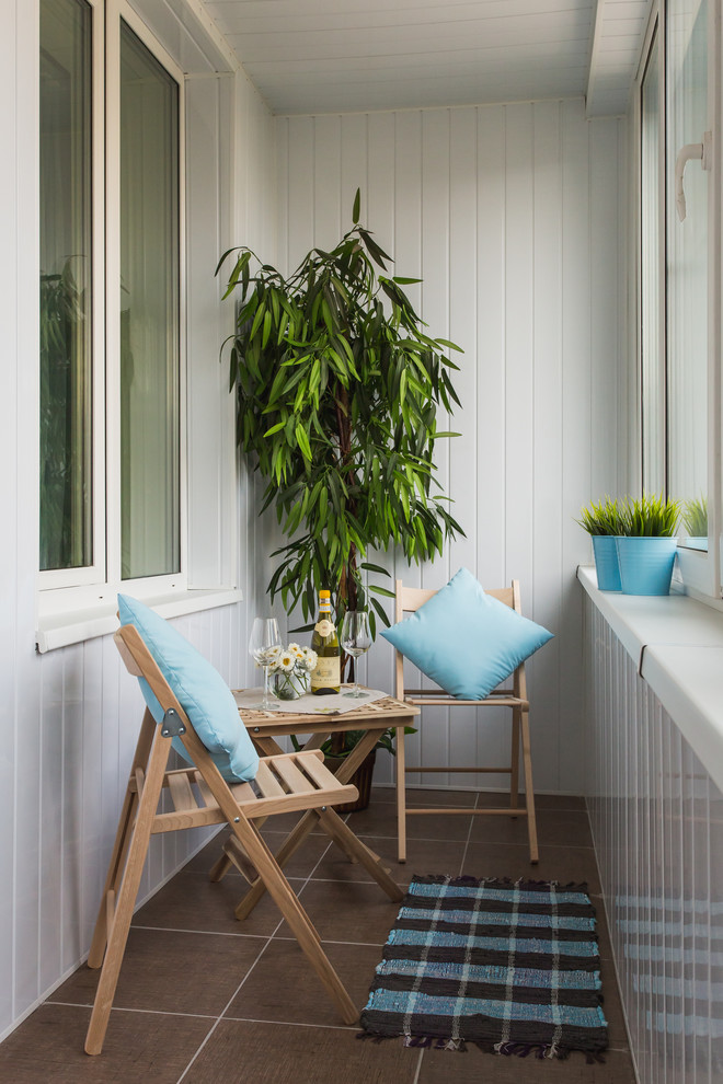 small sized scandinavian balcony with enclosure light toned wood furniture set blue throw pillows black blue stripes mat vertical siding wood wall in white brown tiles floors