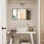 Small Sized Shabby Chic Bathroom Vanity In White White Sink Antique Mirror White Wall Light Fixture White Brick Walls Concrete Floors