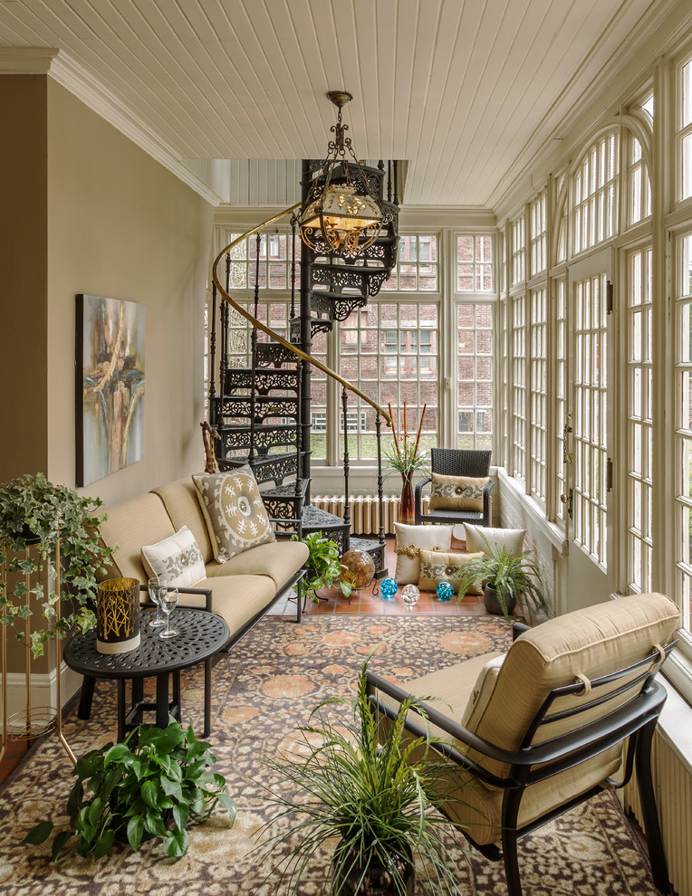 traditional sunroom black iron staircase and gold toned railing in spiral shape luxurious pendant beige seats round top side table in black beige walls white wood siding ceilings