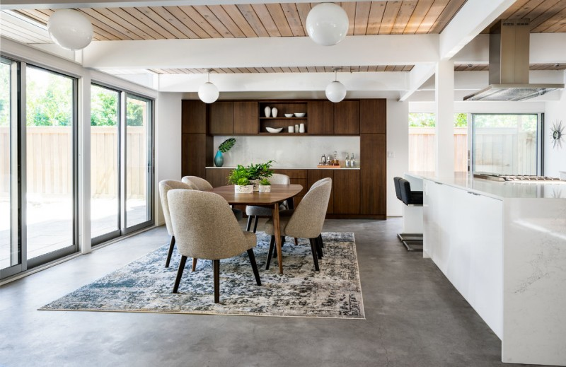 updated mid century dining room Cora dining chairs with dark legs fabric area rug radiant concrete floors walnut flat panel cabinets 1970's light fixtures in white