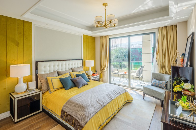 white tufted upholstery headboard in white with black frame yellow bedcover and pillows modern bedisde tables and dressers in black and white white table lamps