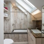Contemporary Bathroom With Slanted Roofs And Skylights Light Wood Walls Pebbles Floors Light Cream Bathroom Vanity With Hardwood Top Undermount Sink In White