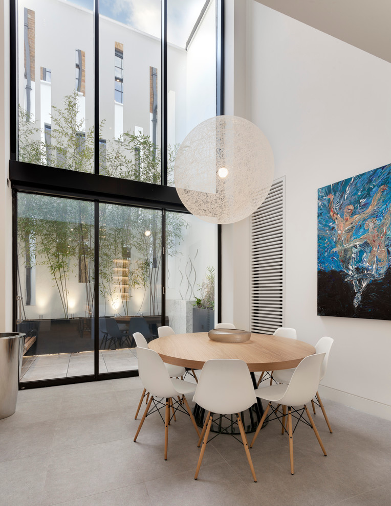 contemporary dining room high glass wall super large string light pendant round top wood dining table scandinavian plastic dining chairs abstract picture