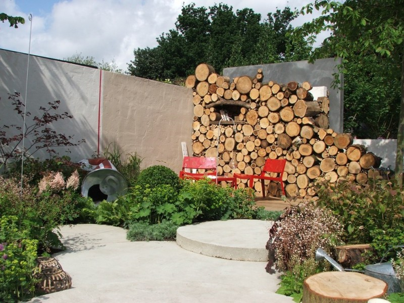 contemporary sunny landscaping design with pile of logs background red painted wood chairs concrete floors concrete fences