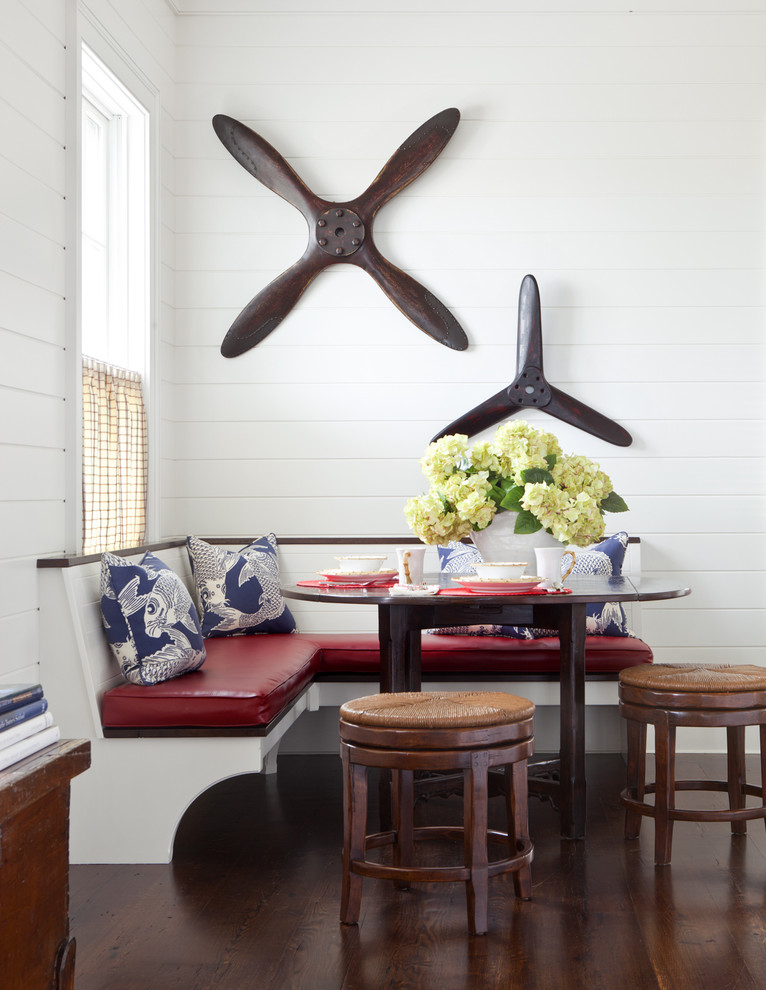 decorative airplane propellers L shaped built in dining bench with red leather seat wood side chairs dark wood floors white siding wood walls