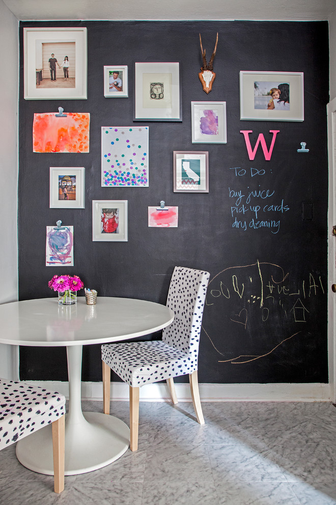 eclectic breakfast nook chalkboard wall system lots of wall arts classic white round top table dalmation patterned dining chairs