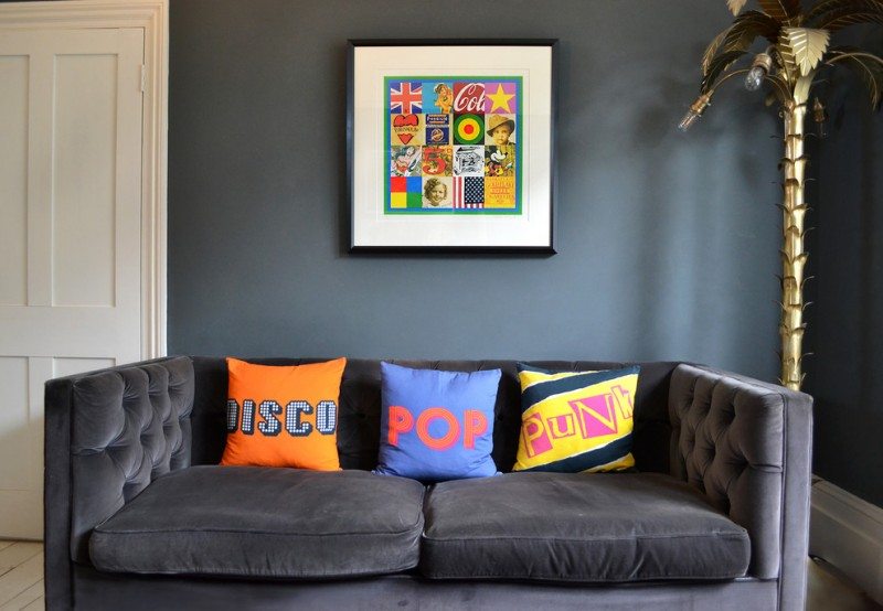 eclectic living room dark blue wall pop art print with frame pop art throw pillows dark blue couch