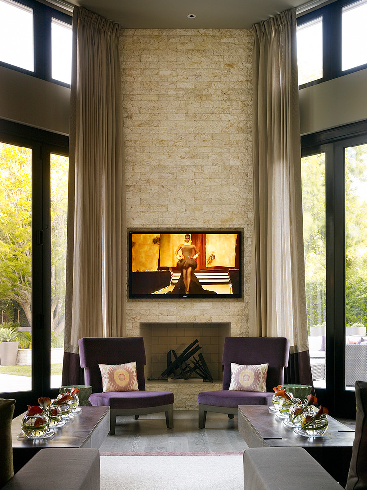 grand contemporary living room full length curtains in grey hard textured natural stone wall firebox with pop painting above purple armchairs with bright throw pillows