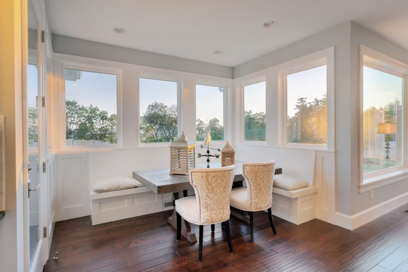 grand luxurious small breakfast nook in white white bench seat dark butcher block table expensive white chairs dark wood floors
