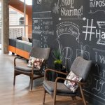 Mid Century Chairs With Smaller Throw Pillows Chalkboard Wall Background Medium Toned Wood Floors