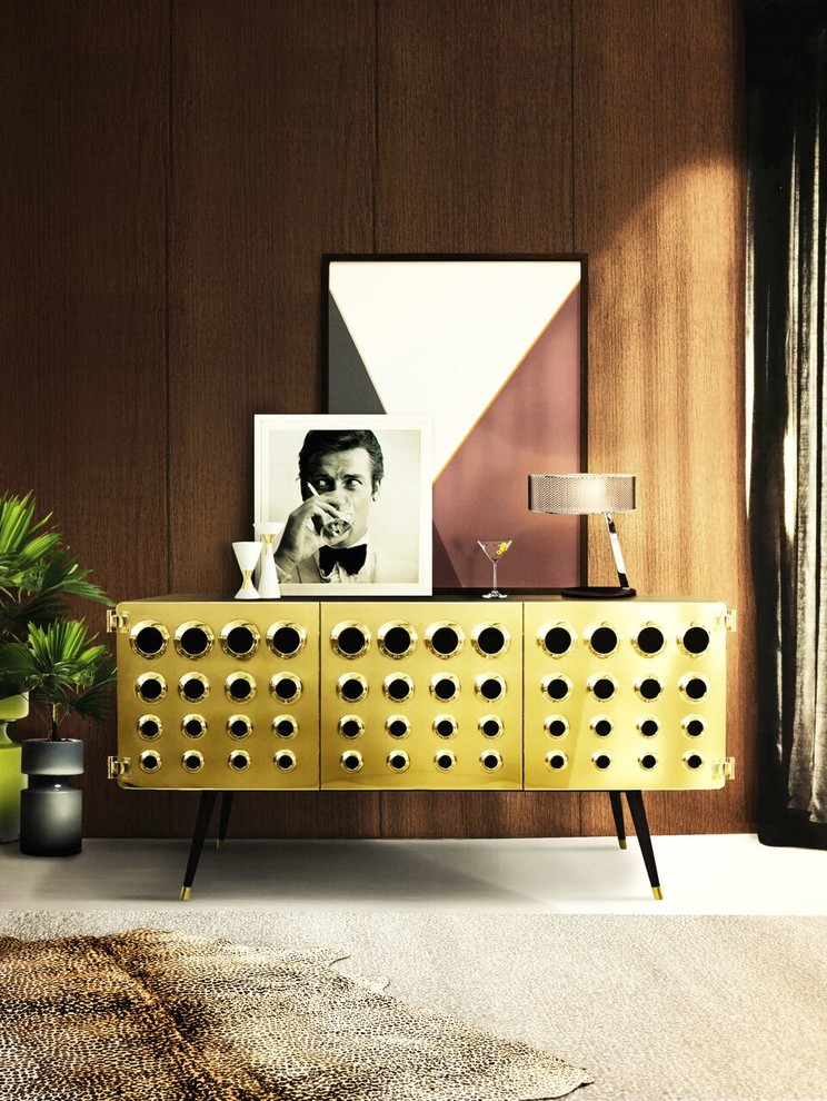 midcentury modern perforated credenza with gold toned surface and pointed & angled legs some ornante pop arts wood walls