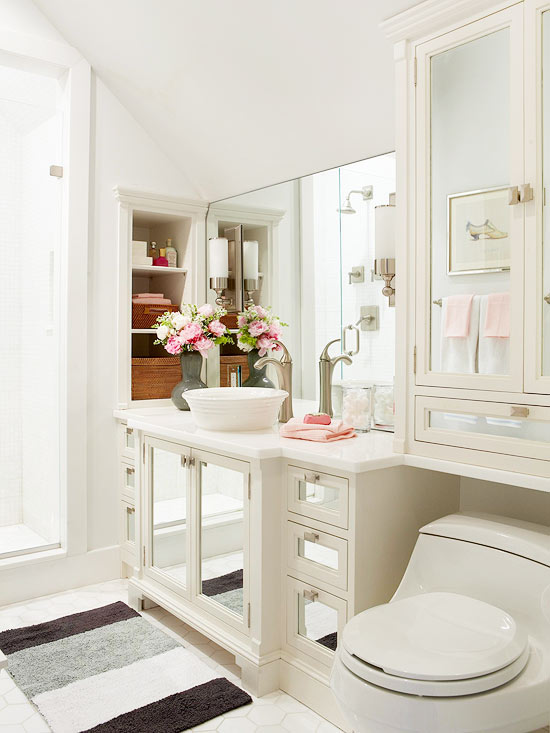 mixed neutral bathroom white ceilings white walls broken white bathroom vanity with glass cabinets' door and marble countertop frameless mirror white toilet