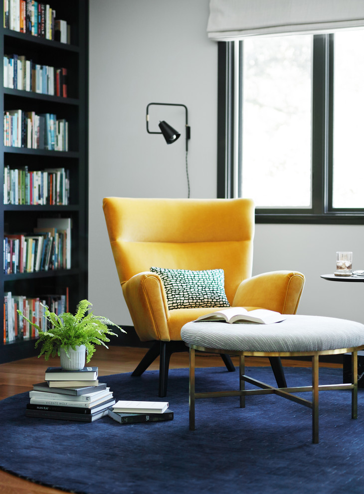 modern vintage armchair in yellow navy blue rug large & black book shelves