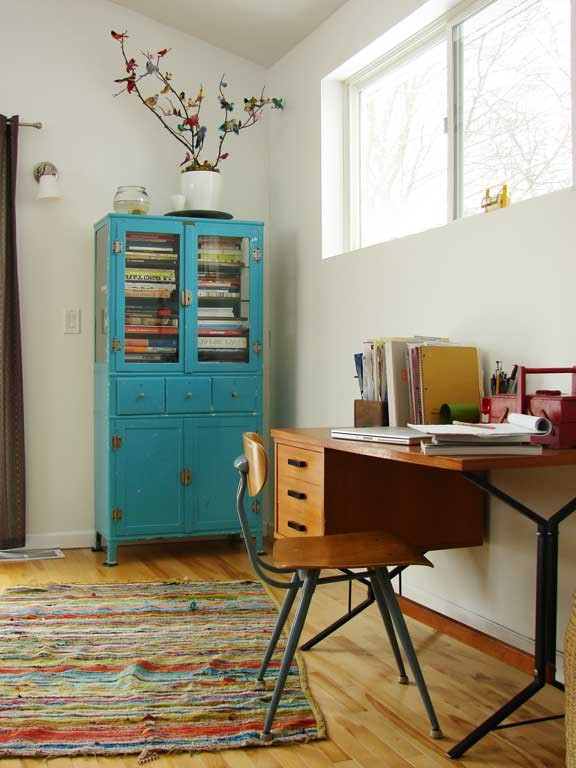 modern vintage home office blue radiant display cabinet wood working desk mid century modern wood chair medium toned wood floors colorful area rug
