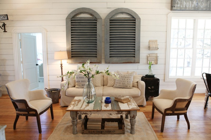 open concept semi formal living room cream sofa slipcover cream chairs medium toned wood floors shabby cream area rug shabby center table vintage style window shutters