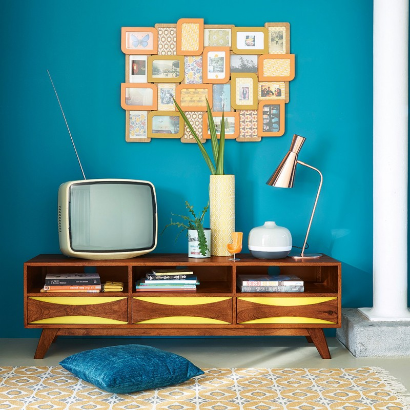 retro style living room bright blue wall color cute cluster of picture frames old fashioned TV set vintage TV console with angled legs