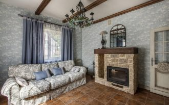 rustic vintage living room standard fireplace with stone surrounding dark brown tiles floors vintage sofa slipcover smaller blue throw pillows blue draperies exposed wood beams blue wallpapers