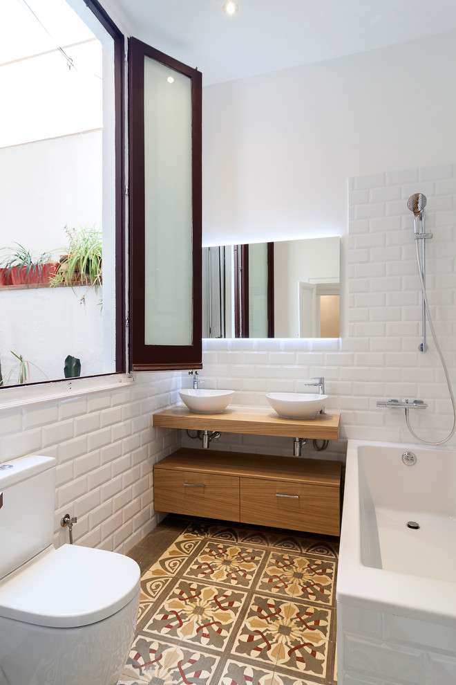 scandinavian bathroom design white brick walls morrocan tiled floors white toilet a pair of white sinks flat paneled wood cabinets white bathtub