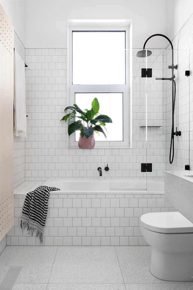 scandinavian bathroom white square tiled bathtub white square tiled walls ceramic tiled floors white toilet black stained bathroom fixtures