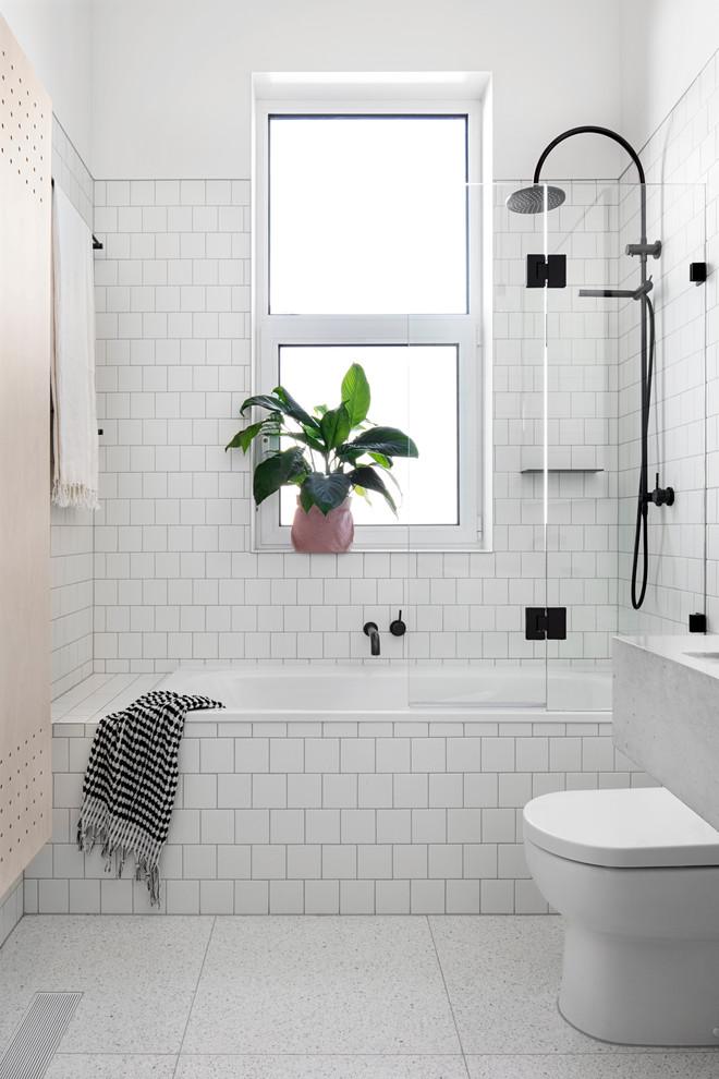 scandinavian bathroom white square tiled bathtub white square tiled walls ceramic tiled floors white toilet black stained bathroom fixtures