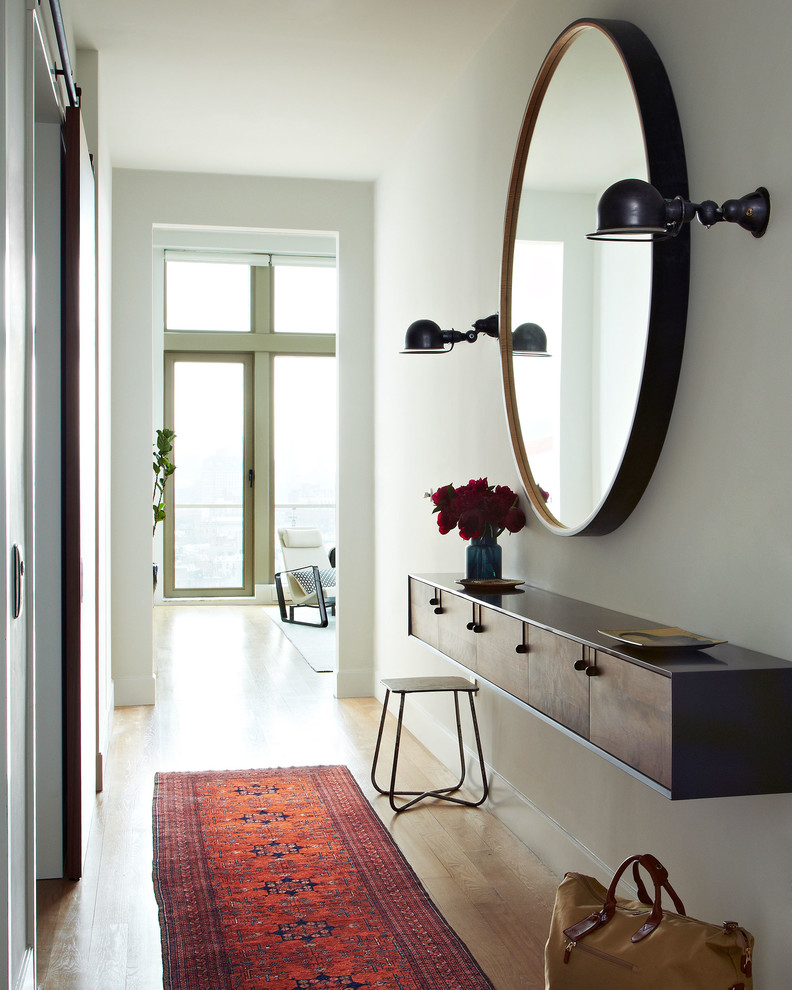 scandinavian entryway oversized round shaped mirror with darker frame darker floating hall console table thin legs side chair Moroccan area rug medium toned wood floors white walls