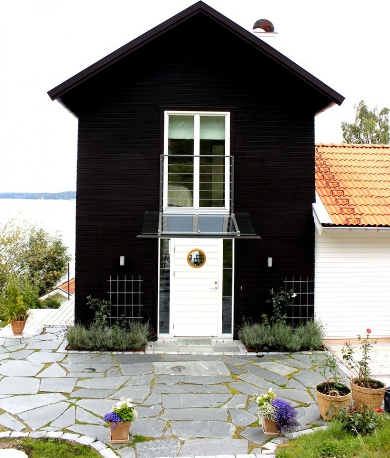 scandinavian exterior in solid black white trimed window white entry door with glass shading