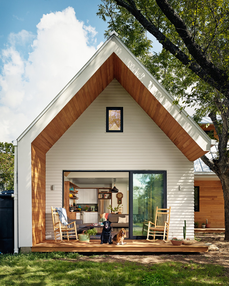 scandinavian exterior open gable roof model a smaller central window with black frame white wood siding exterior walls wood siding slanted panels black framed glass sliding door and window